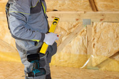 Construction mason worker with building level and screwdriver on attic with environmentally friendly. And energy efficient thermal insulation rockwool Royalty Free Stock Photos