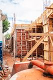 Construction of a masonry house. House made of bricks, steel rebars and concrete. Structural parts of a house. Wooden support structure royalty free stock images