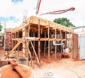Construction of a masonry house. House made of bricks, steel rebars and concrete. Structural parts of a house. Wooden support structure stock image