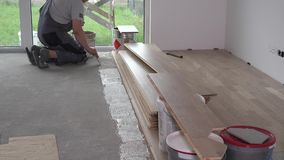 Construction master put adhesive glue on masonry floor. Preparation works for floor board laying. Zoom in shot stock footage