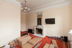 Construction materials,  furniture, TV and phone  are on the floor in apartment with retro  fireplace  of the hotel Stock Images