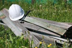 Construction materials on the grass. Construction materials lie on the grass hammer and helmet Royalty Free Stock Photo