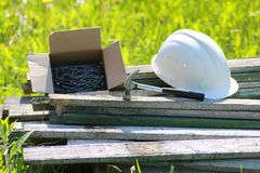 Construction materials on the grass. Construction materials lie on the grass hammer and helmet Stock Photography