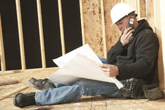 A construction  men working. A construction  man working with a plant a calling with his phone Stock Image