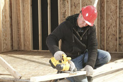 A construction  men working. A construction  man working using a saw Royalty Free Stock Images