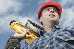 A construction  men working outside. A construction  man working outside holding a saw Stock Photo