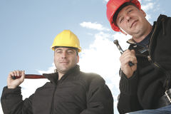 A construction  men working outside. Two construction worker men working outside with hammer Royalty Free Stock Photo