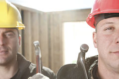 A construction  men working outside. Two construction worker men working outside with hammer Royalty Free Stock Images