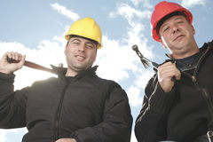 A construction  men working outside. Two construction worker men working outside with hammer Stock Images