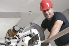 A construction  men working. A construction worker with red helmet working with a saw Stock Image