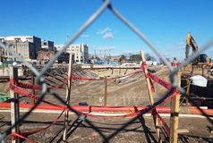 Construction with with metal fence, beams, machines, and red danger tape in Alexandria, Virginia stock photography