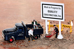Construction Miniatures. Macro of miniatures of team of construction workers, Work in Progress sign, and equipment at a work site Royalty Free Stock Images