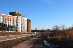 Construction of modern apartment buildings in Novosibirsk in autumn. Near the technological road royalty free stock image