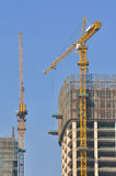 Construction of modern architecture. Buildings under construction and tower crane is working, with blue sky background Royalty Free Stock Image