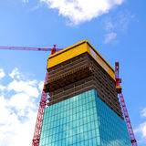 Construction of a modern building. Construction of a modern high rised building with construction plattform and two cranes Stock Photography