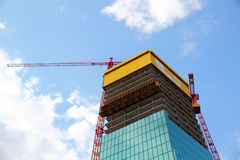 Construction of a modern building. Construction of a modern high rised building with construction plattform and two cranes Stock Photo