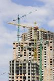 Construction of modern building. Construction site of modern highrise building with cranes in operation stock photos