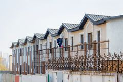 Construction of modern buildings. Masters work on finishing hou. Se royalty free stock image