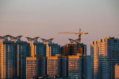 The construction of modern high-rise buildings at sunset light with crane, Voron Stock Photography