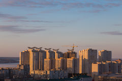 The construction of modern high-rise buildings at sunset light with crane Royalty Free Stock Image