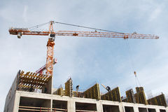 Construction of monolithic apartment house, tower crane lifts th Royalty Free Stock Image