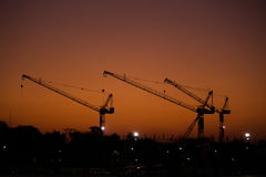 Construction. In morning. Sky color is orange. crane is silhouette Stock Image