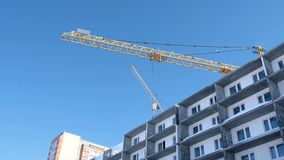 Construction of a multi-storey building. Construction crane. Unfinished multi-storey house with windows. Construction of a multi-storey building. Construction stock video footage