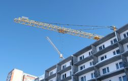 Construction of a multi-storey building. Construction crane. Unfinished multi-storey house with windows. Construction of a multi-storey building. Construction Royalty Free Stock Images