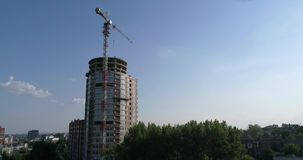 Construction of a multi-storey building, Tower crane, Unfinished multi-storey building, Building a high rise, Panoramic. View, aerial, from the air stock footage