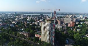 Construction of a multi-storey building, Tower crane, Unfinished multi-storey building, Building a high rise, Panoramic. View, aerial, from the air stock video footage