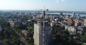 Construction of a multi-storey building, Tower crane, Unfinished multi-storey building, Building a high rise, Panoramic. View, aerial, from the air stock video