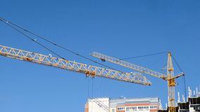 Construction of a multi-storey buildings. Two construction cranes against the sky work at the construction site. Construction of a multi-storey buildings. Two stock footage