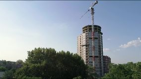 Construction of a multi-storey high house, a tower crane at a construction site, a view of the construction of a modern. High-rise building, an urban landscape stock video footage
