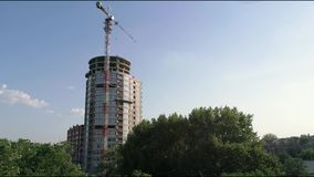 Construction of a multi-storey high house, a tower crane at a construction site, a view of the construction of a modern stock footage