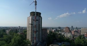 Construction of a multi-storey high house, a tower crane at a construction site, a view of the construction of a modern stock video footage