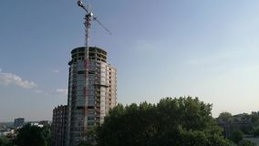 Construction of a multi-storey high house, a tower crane at a construction site, a view of the construction of a modern. High-rise building, an urban landscape stock footage