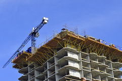 Construction of multi-storey residential house. Building high-rise crane and multi-storey building on a background of blue sky Stock Photos