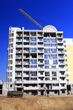 Construction of multistorey modern house with hoisting crane Royalty Free Stock Photo
