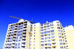 Construction of multistorey modern house with hoisting crane Stock Photography