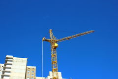 The construction of a multistory building. Construction of multistory building with a construction crane Stock Photos