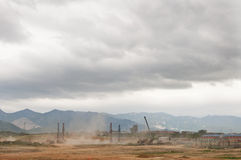 Construction and Nature. Dust flies with construction in developing Asia with mountains in the background Stock Photography