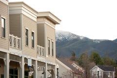 Construction neuve contre la montagne recouverte par neige Image stock