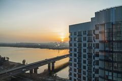 Construction of new apartment buildings at sunset. Construction of new apartment buildings in Kiev. view of the river Dnieper and the bridge evening at sunset royalty free stock image