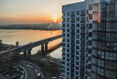 Construction of new apartment buildings at sunset. Construction of new apartment buildings in Kiev. view of the river Dnieper and the bridge evening at sunset royalty free stock images