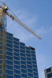 Construction - new blue glass building and crane Royalty Free Stock Photo