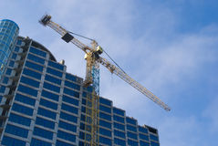 Construction - new blue glass building and crane Stock Photography
