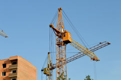 Construction of the new brick building by means of the elevating Royalty Free Stock Photo