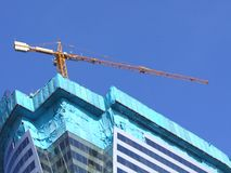The construction of new glass building and crane. With blue sky background Stock Photo