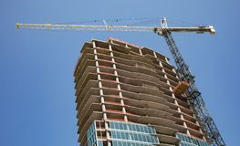 A crane rissing above a new high rise building under construction. royalty free stock images