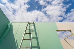 Construction of new and modern modular house. Construction new and modern modular house from composite sip panels. Low angle view photo of metal ladder standing royalty free stock photography